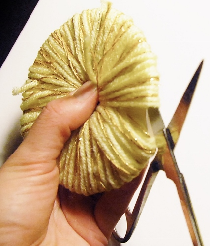 Slide scissors in between the 2 layers of paper and cut the yarn around the edge.