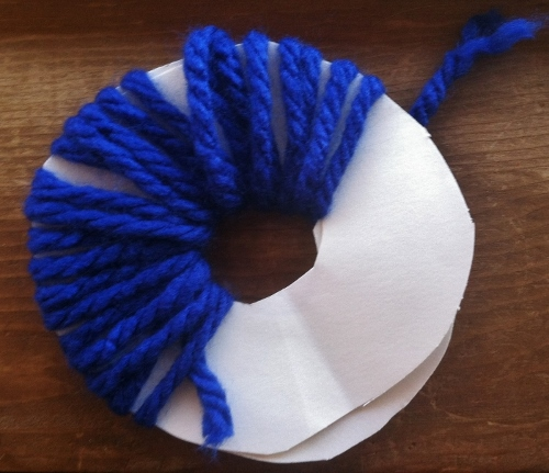 Take a length of yarn (about the length of your armspan) and weave it around the circle.
