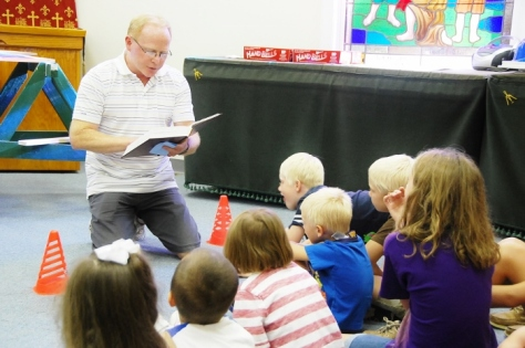 Our pastor reading the Bible to the kids