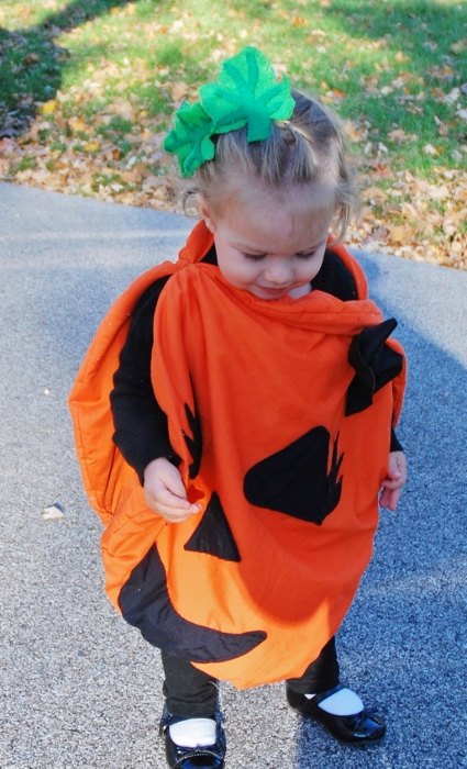 Baby wearing the pumpkin costume (with modifications of eyelashes and bow!) and hand-sewn leaf-barettes