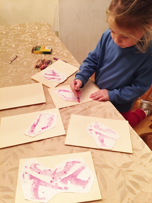 Baby working on Christmas thank-yous. Those pink prints were made by pressing a dragon fruit onto paper (the dragonfruit is a great source of pink ink!)