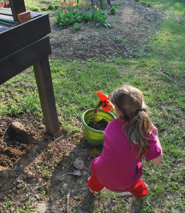 Filling up a pot with dirt; really putting her back into it! haha